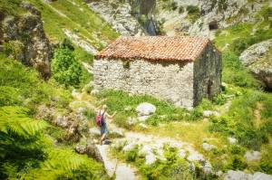 PICOS DE EUROPE, SPAIN - JULY 9, 2016: The ancient stone shed wi